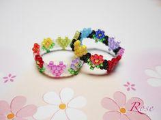 ♪商品詳細 ☆オーロラパール&黒に虹色のハート&花が可愛いビーズステッチリングです。☆デリカビーズで編んでいますので、しなやかで、とても付け心地が良いです。 ☆サイズ範囲は12.5〜13.5号くらいで、幅は0.8cmくらいです。 ☆完成品の為、サイズ変更はできませんので、お好きな指で楽しんで下さい。♪コメント☆ビーズを水にぬらしたり、強く擦ると色落ちすることがありますので  取り扱いには十分注意して下さい。 ☆手作りをご理解の上、ノークレーム・ノーリターンでお願いします。