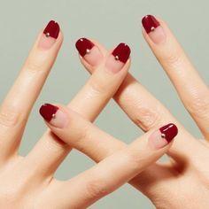 Trends rote Nägel halb lackiert mit goldenen Pünktchen
