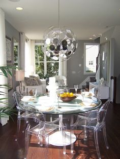 Glass dining table and acrylic chairs with black white design