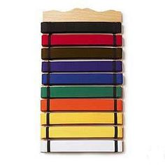10 Level Belt Display A showcase for your achievements! - Wooden belt display. - Holds up to 10 belts. - Any size belt will fit easily. - Mounts easily to a wall. - Elastic straps hold belts in place.