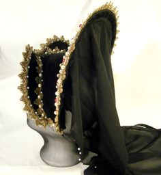 This special french hood is a statement piece and will sure be a head turner at renfaires. It is made with black velour, covered with golden lace and German woven lace. The hood is covered with hundreds of hand sewn on, glass and acrylic pearls in cream white, red and golden. The crown part is adorned with golden drops, fastened with metal pins, this adorned crown part is easily detachable and attachable through velcro. The long black veil is attached to the crown part and the edge is…