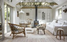 Ei stue i lyse farger med en hvit sofa, en kurvstol og bjelker og gulv i tre.