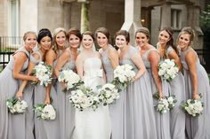 bride and her maids before they head to the church. maids chose their style of pale grey gown. their classic all white bouquets are garden roses, ranunculus, button camomile, spray roses, dusty miller, eucalyptus and bay leaf.