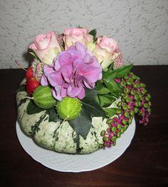 Bloemstukje op pompoen met rozen, sier komkommer, appeltjes en hortensia