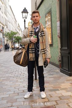 Men's street style | Urban Suave - Always be suave on the run with this formal look of a navy suit with a trench coat, an expensive scarf and a statement duffle bag. Yet add a hint of casual with a pair of white trainers. | Shop the look at The Idle Man