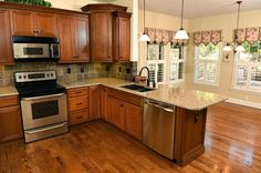 Kitchen with wood floors, stainless steel appliances, quartz countertops and eat-in area.