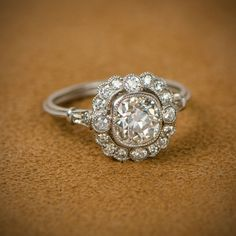 A stunning vintage cushion cut diamond engagement ring, set in platinum and adorned with a halo of d Square Halo Engagement Rings, Floral Engagement Ring, Wedding Rings Solitaire, Cushion Cut Engagement Ring, Princess Cut Engagement Rings, Wedding Rings Vintage, Vintage Engagement Rings, Solitaire Engagement, Bridal Rings