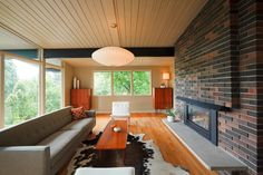 Immense floor to ceiling glass allows sunlight throughout this warm living room…