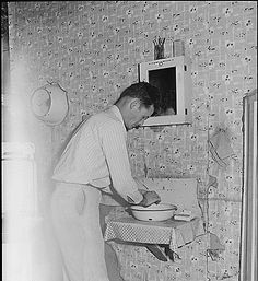 Richard Hughes, a miner, washes his hands in the kitchen of his four room house for which he pays $9 monthly. Panther Red Ash Coal Corporation, Douglas Mine, Panther, McDowell County, West Virginia., 08/26/1946