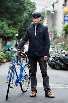 Sam Shen Yang, designer. Jacket from Uniqlo, pants from H&M, shoes from Clarks, hat from Brixton, glasses from Ray Ban, bicycle from Raych. Tie is handmade.
