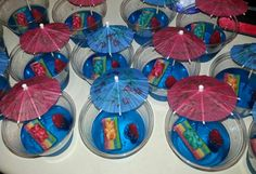 """Pool/beach party jello cups!!   3 boxes blue jello made according to box directions Let set over night Ur choice candy for decorating I used sour multi colored strips cut in half for """"blanket"""" and swirled gummie bears and sweedish fish  AWESOME FOR KIDS!!!!!!!  could probably be fun for adults if added a little vodka.       (Makes about 15 cups)"""
