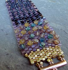 """Gorgeous Peyote Stitch Bracelet. Cubes glass beads make up the foundation of the bracelet. Detailed with Czech Flat Round Faceted Beads and 3 mm Purple Bi-cone Crystals. Finished with Gold Triangle Beads and a Large Goldtoned clasp. 7"""" in length."""