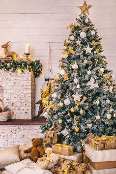 Weihnachtsbaum mit viel Schmuck, weiße Christbaumkugeln, goldene Schleifen, viele Weihnachtsgeschenke unter dem Baum