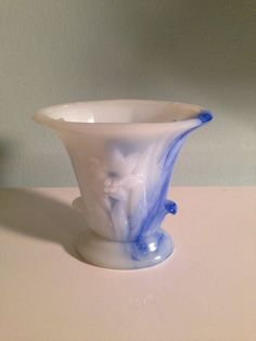 """Vintage 1930s Akro Agate Marbleized Blue and White Slag Glass Mini Vase by PhineasStreet on Esty.  What a unique-looking little vase! The vase is made from a mold out of blue and white marbleized glass and measures 5"""" tall. The oval opening is 4 3/4"""" x 3"""". It has a beautiful Lilly on each side and the blue color is quite vibrant.  I have one and use it for my as a vintage makeup brush holder on my vanity or use as a vintage toothbrush holder!"""