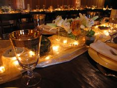 We designed and made our own floral arrangements. Interspersed on the tables were nests with gold eggs, pairs of gold birds, amber glass votive holders, gold paper cones with fresh flowers, pearl strands, gold-flecked tulle runners lit with white strand mini lights.  The tulle was from JoAnn Fabric and Craft Stores.