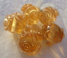 Scrolls of gold  handmade lampwork bead set by FlamingEck on Etsy, £10.00