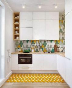 Небольшая белая кухня с яркими геометрическими фигурами на полу и стене