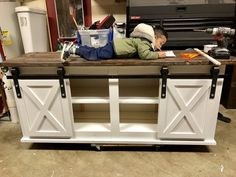 *Toddler approved* A classic colorway. Custom 80-inch media console table with sliding barn doors. The customer is coupling this with two massive floating shelf beams. Ready for delivery! White base with dark stained top.