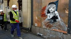 """British graffiti artist Banksy has criticised the treatment of migrants in Calais with a mural opposite the French embassy in London that depicts a crying Cosette, the orphan girl in the novel """"Les Misérables"""", engulfed by a cloud of tear gas."""