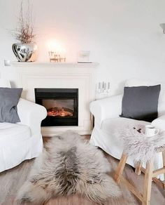 The white of the chair makes this look radiant. In between, accents made of natural m Candles In Fireplace, Living Room With Fireplace, Cushions, Pillows, Home Accents, Cushion Covers, Shag Rug, Sweet Home, Relax