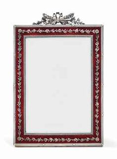 A LARGE FABERGÉ PHOTOGRAPH FRAME, WORKMASTER VIKTOR AARNE, ST PETERSBURG, 1899-1904. Rectangular, enamelled in translucent scarlet red over a wavy guilloché ground, applied with silver laurel branch and berry bands, flanked by rosettes at corners, all within a ribbon-tied reeded border, surmounted by two ribbon-tied torches and laurel branches.
