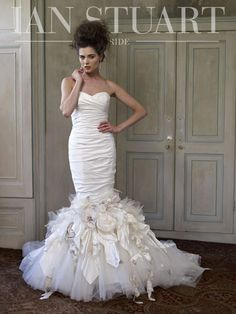 A show-stopping gown designed for maximum impact. The sexy silhouette is exaggerated with tight draping that moulds the body to the knee where an explosion of flowers, tulle, and petals cascade into a long rambling train. The matching voluminous tulle jacket (not shown) is scattered with the same details as the train.