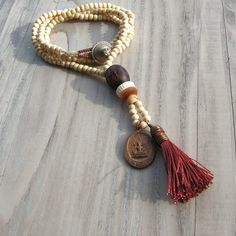 Mala Tassel Necklace in Rust and Cream Wood with Buddhist Amulet Pendant