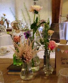 Example of eclectic mix of vases, yours would have vintage  tealights in between and little succulents in between, this is shown on a hessian runner- Emmas Wedding and Events