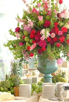 Beautiful food table centerpiece of French tulips, snapdragons, larkspur, roses, peonies, viburnum and green apples created by celebrity event designer Scot Wedgeworth.  www.scotgwedgeworth.com