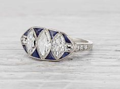 Art Deco ring made in platinum and set with three EGL certified marquise cut diamonds weighing approximately 1.30 carats total. The center diamond has G-H color and SI1 clarity. Accented with sapphires, single cut and bullet cut diamonds. Signed Tiffany & Co. Circa 1925.