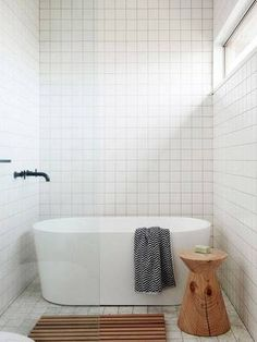 minimalist bathroom white bathroom and wooden stool by tub