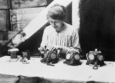 A woman war worker fixes nose clips on to gas masks at a factory in Bermondsey, London, 1918.  Lewis G P  © IWM (Q 28593)