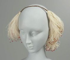 Woman's headdress, French, worn in Boston, mid-19th century. MFA, 52.1266. Silk-covered wire band ending at both ends in white ostrich feather, each plume tipped with coral chenille.