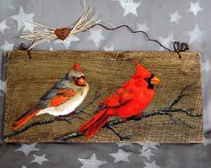 Un par de cardenales sentarse en una rama desnuda, pero que buscan bayas, por lo que se trasladarán a una rama más abundante. Estos alegres pájaros están pintados en un tablero de establo rústico recuperado de un antiguo granero de Ozarks, caerse de vejez y erosión. La Junta se cuelga con un gancho de alambre de alambre de corral oxidado y adornado con un corazón de lata oxidado del faux y un poco de rafia.  Haga clic en la ficha de envío y políticas para ver las tarifas de envío para este…
