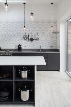 Simplicity of lighting and pattern of the backsplash hold your attention in this Scandinavian kitchen