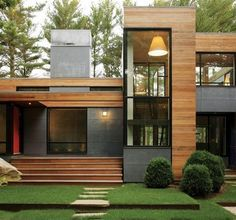 Modern house dark grey with light horizontal wood accent areas, dark door frames