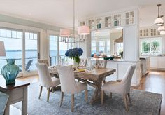 Gorgeous beach house dining area opening onto a classic white kitchen beyond