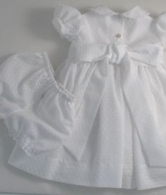 A sweet little dress and matching bloomers custom made for a baby girl. Ideal for a Christening/Baptism or important function.  NB. This is custom made using our own original and copyrighted pattern, exclusive to ourselves. Description:-  The dress has horizontal tucks across the bodice, a peter pan collar and little puff sleeves. Ties from the side seams to make a bow at the back.  Fully lined with white cotton lawn and netting. Matching bloomers are included.  Sizes:- 3m, 6m, 12m, 18m, 2y…