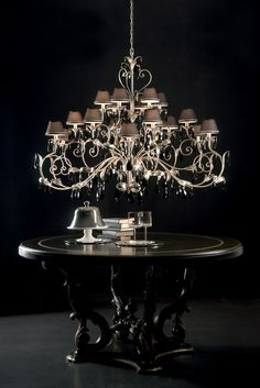 Discover the Large High-End Black Crystal Silver Chandelier at Juliettes Interiors. This gorgeous ornate chandelier is handmade in Italy providing a superbly romantic focus. The beautifully curved wrought iron frame is entwined with leaves and finished with silver leaf, and includes a profusion of contrasting black and clear Bohemian crystal pendants for a dramatic focus. Complete with 18 luxurious bronze and silver silk shades.