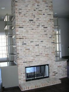 Fireplace Designs by Maria Kay...like the color of this brick, would do a chunky, dark brown, reclaimed wood mantel