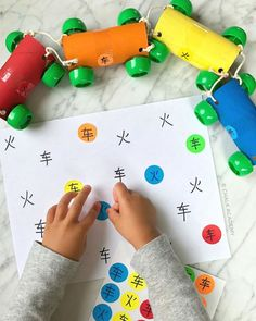 Recycled cardboard roll train and sticker matching for my vehicle-obsessed son! Teaching Chinese characters 火车 / 火車 (huǒchē / train) in both simplified and traditional Chinese while speaking Mandarin.   DIY train toy is made of toilet paper rolls, paint, and recycled bottle caps. Favorite dot stickers and videos of the activities explained on Instagram!