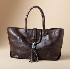 Here's a bag that aims to please by adapting to the needs of the moment. Two interior leather pockets snap in for a smaller look or out as you please. The style-defining tassel clips on or off for another look. With braided detailing, stitched edges and rolled handles. Distressed, vegetable-tanned leather ages gracefully