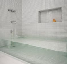 This 'invisible' bathtub, designed by Stern McCafferty Architecture & Interiors, features a thick sheet of glass between two tile walls
