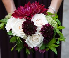 Bridesmaids carry colorful bouquets of white roses and deep purple dahlias backed with bright green leaves.
