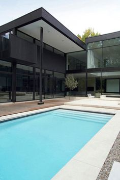 This two-storey modern residence, called 44 Belvedere, is located on a wooded lot in Oakville, Ontario. Imagined by Guido Costantino, the black palette consists of stucco, concrete, brick, anodized siding and a mix of opaque and transparent glass.