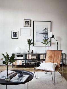 Tavelvägg och läderfotölj i detta vardagsrum