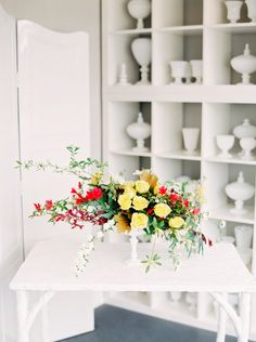 Flower arrangement with greens and yellow roses