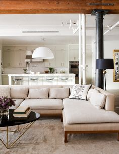 industrial modern.  love the exposed wood beam, pipes, low back sofa, black tripod floor lamp, and white kitchen.  Christiane Lemeiux