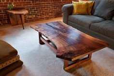 This custom slab coffee table features a beautiful piece of claro walnut and mostly live edges.