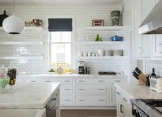 The all white kitchen of a Novogratz-designed vacation home has glossy tile walls, white cabinets with gold handles, open shelving, marble countertops and hanging white globe light. Kitchen Redo, Kitchen Shelves, New Kitchen, Kitchen Dining, Kitchen Remodel, Kitchen Cabinets, White Cabinets, Inset Cabinets, Design Kitchen
